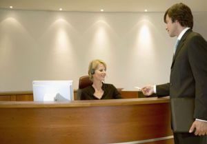 Businessman Standing at a Reception Desk Giving a Business Card to the Receptionist